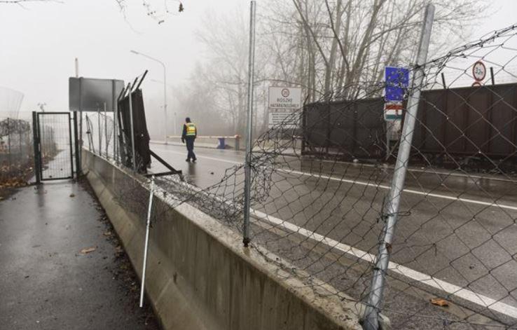 Videón, ahogy egy nagyobb migránscsoport megpróbálja áttörni a kerítést a magyar határon, a rendőrök figyelmeztető lövést adtak le