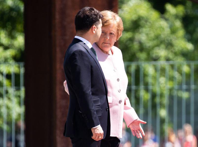 Merkelt megszédítette a hőség, remegve hallagtta a himnuszt – videó